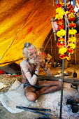 A holyman smokes hashish in a pipe at the Kumbha Mela festival 2007, the largest gathering of people on the planet. 30 million Hindus and holy men known as Sadhus come to cleanse their sins in the Gan... - Tom Parker - 20-02-2007