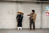 A man giving money to a beggar dressed in traditional Japanese dress, Tokyo. - Tom Parker - 04-04-2007