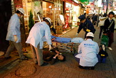 Firefighters and paramedics help passed out drunk man in Tokyo, alcohol abuse is an increasing problem in Japan. - Tom Parker - 04-04-2007