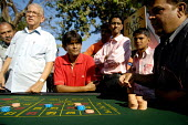A mock casino where fake money is used at The Mumbai Derby, where the citys rich and famous come to watch the horse racing and bet. Gambling in India is largely illegal. - Tom Parker - 2000s,2007,Asia,asian,asians,bet,bets,betting,boy,boys,button,buttons,casino,child,CHILDHOOD,children,course,courses,gamble,gambler,gambling,group,groups,imitation,India,Indian,indian subcontinent,Ind
