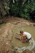 Local miner panning for diamonds in a stream near Kisangani. Rwandan and Ugandan forces have strived to win control of the profitable gem mines in DRC. Kisangani, Zaire-Congo. - R. Chalasani - 31-08-1990