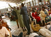 Reverend John Nduati puts his hand on a woman with HIV to cure her during a service at Gods Power Church and World Center of Healing. In a country where health care is minimal and most cant afford tre... - R. Chalasani - 11-05-2003