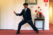 Old blind Chinese man doing Kung Fu with his stick in the Chinese Old peoples' home, Cherish House (Hang Fook) in Digbeth, Birmingham - Timm Sonnenschein - 2000s,2004,accommodation,asian,Birmingham,blind,blindness,bme minority ethnic,cantonese,chinese,cities,citizen,city,communities,community,Diaspora,disabilities,disability,disable,disabled,disablement,
