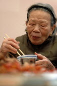 Elderly Chinese woman having lunch in the Chinese Old peoples home, Cherish House (Hang Fook) in Digbeth, Birmingham - Timm Sonnenschein - 2000s,2005,accommodation,adult,adults,age,ageing population,asian,Birmingham,cantonese,chinese,chop,cities,citizen,city,communities,community,Diaspora,east,eat,eating,Elderly,emigrated,emigration,FEMA