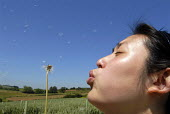 A young Chinese woman blowing a dandelion clock. - Timm Sonnenschein - 17-06-2006