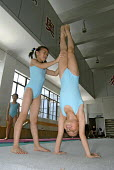 A young girl performing a handstand training in gymnastics for future Olympics at the Shanghai Hongkou Youth Sports School - Timm Sonnenschein - 2000s,2006,agility,asia,athlete,athletes,athletic,balance,balanced,bar,bars,Chinese,edu education,educating,education,exercise,exercises,exercising,female,females,games,girl,girls,GYMNAST,gymnastic,gy