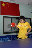 A girl playing ping pong, training for future Olympics at the Shanghai Hongkong Youth Sports School - Timm Sonnenschein - ,2000s,2006,agility,asia,banner,BANNERS,Chinese,east,education,exercise,exercises,female,females,flag,FLAGS,games,girl,girls,Olympia,Olympics,paddle,paddles,PE,people,person,persons,physical,PLAY,play
