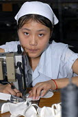 A worker sewing trousers for export in a textile factory in Shanghai - Timm Sonnenschein - 25-08-2006