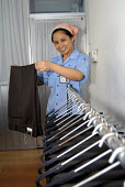 A worker presenting trousers which are ready for export in a textile factory in Shanghai - Timm Sonnenschein - 25-08-2006