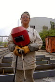 Woman Chinese welder at a wharf in Pudong, Shanghai - Timm Sonnenschein - 2000s,2006,boat,boats,capitalism,capitalist,Chinese,dark,dock,Dong,EBF Economy,export,EXPORTS,FEMALE,force,grease,harbor,harbors,harbour,harbours,Huangpu,import,IMPORTED,IMPORTS,industrial,Industries,