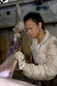Heavy labour, a young Chinese man sanding and polishing a large propeller in a wharf in Pudong, Shanghai  � - Timm Sonnenschein - 17-08-2006