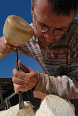 Sculptor working on a piece of art in Digbeth, Birmingham - Timm Sonnenschein - 2000s,2006,ace art arts culture,art,artist,artistic,ARTISTS,artwork,artworks,away,Birmingham,block,blocks,by hand,carving,chipping,chisel,concentrated,concentration,creating,creative,focus,focused,mak