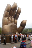 Tourists touching a life size replica hand of the 88 meter high Amitabha Buddha statue, Wuxi, China - Timm Sonnenschein - 02-09-2006