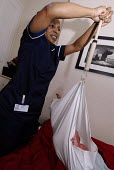 A midwife weighing a heavy baby on a home visit, Birmingham - Timm Sonnenschein - 2000s,2007, care,adult,adults,babies,baby,BAME,BAMEs,Birmingham,black,BME,BME Black minority ethnic,bmes,care,check,checking,child,CHILDHOOD,children,Chinese,cities,city,diversity,EARLY YEARS,ethnic,