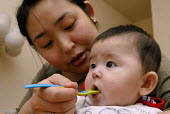 Chinese mother feeding her mixed race baby - Timm Sonnenschein - 27-12-2007