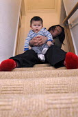 Chinese mother sitting in a staircase with her mixed race baby - Timm Sonnenschein - 04-01-2008