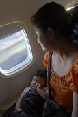 A baby girl sleeping in her mums arms on an aeroplane - Timm Sonnenschein - 2000s,2008,,comfort,travel,adult,adults,aeroplane,aeroplanes,air transport,aircraft,airline,airplane,airplanes,airport,AIRPORTS,Asian,asians,asleep,aviation,babies,baby,BAME,BAMEs,being,BME,bmes