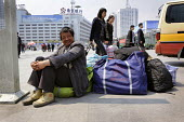 Migrant workers waiting outside the railway station to leave Shanghai, China and return to the countryside as jobs are lost during recession - Timm Sonnenschein - 2000s,2009,bag,Asia,Asian,bag,baggage,bags,BUILDING,BUILDINGS,Chinese,cities,city,construction,country,countryside,Credit Crunch,crisis,Diaspora,DOWNTURN,EARNINGS,east,EBF,Economic,Economy,employee,