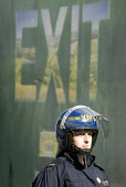 Police officer in riot gear with an advertisement saying Exit, Dudley - Timm Sonnenschein - 17-07-2010