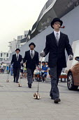 Performers walk outside the English pavilion during the Expo 2010, Shanghai with bowler hats and walking toy dogs. - Timm Sonnenschein - Chinese,2010,2010s,ACE,culture,outside,performance,performer,performers,performing,satire,satirist,satirists,Shanghai