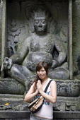 A young woman posing for a photograph in front of a rock carving of the Bodhisattva Vajrapani at the Feilai Feng grottoes on the �Buddhist �Lingyin temple site, �Hangzhou, China - Timm Sonnenschein - 16-08-2010