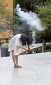 A young woman offering burning incense, a symbolic offering, �Buddhist �Lingyin temple site, �Hangzhou, China - Timm Sonnenschein - 16-08-2010