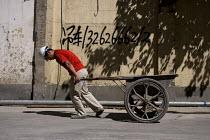 A worker pulling a wheelbarrow on a construction site, Shanghai - Timm Sonnenschein - 20-08-2010