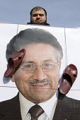 A protester holding a portrait of Pervez Musharraf with sandals in his face, as he is giving his first public speech the day after forming a new political party, Handsworth, Birmingham - Timm Sonnenschein - , Protest,2010,2010s,activist,activists,Birmingham,CAMPAIGN,campaigner,campaigners,CAMPAIGNING,CAMPAIGNS,DEMONSTRATING,DEMONSTRATION,DEMONSTRATIONS,giving,insult,insulting,party,portrait,PORTRAITS,Pro