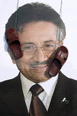 A �portrait of Pervez Musharraf with sandals in his face, as he is giving his first public speech the day after forming a new political party, Handsworth, Birmingham - Timm Sonnenschein - 2010,2010s,Birmingham,giving,insult,insulting,party,public,rude,rudeness,shoe,shoes,speech,West Midlands