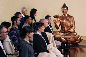 Members of the Triratna Buddhist Order meditating in the shrine room of the Birmingham Buddhist Centre infront of a western Buddha figure - Timm Sonnenschein - 11-10-2009