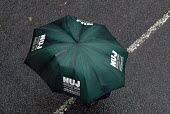 NUJ member walking with an NUJ umbrella Right to Work protest on the opening day of the Conservative Party conference in Birmingham - Timm Sonnenschein - , Protest,2010,2010s,activist,activists,Birmingham,CAMPAIGNING,CAMPAIGNS,conference,conferences,DEMONSTRATION,member,member members,members,NUJ,opening,Party,people,protest,PROTESTER,PROTESTERS,protes