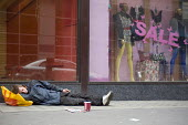 A homeless young man sleeping and begging in central London infront of a store with a Sale. - Timm Sonnenschein - 15-10-2010