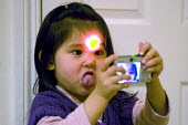 A three year old girl taking self portraits with a compact digital camera -making faces. - Timm Sonnenschein - 2010,2010s,Amateur Photographer,BAME,BAMEs,BME,bmes,camera,cameras,child,CHILDHOOD,children,chinese,digital,diversity,ethnic,ethnicity,female,females,girl,girls,having fun,identity personal,infancy,in