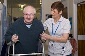 An NHS rehab assistant helping a patient recovering mobility, Moseley Hospital, Birmingham - Timm Sonnenschein - 18-11-2010
