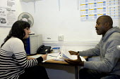 A volunteer worker helping a man seeking advise at the Handsworth Citizens Advice Bureau, which is facing closure due the Birmingham City Council withdrawing 600,000 funding for all five walk in advic... - Timm Sonnenschein - 04-02-2011