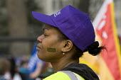 A UNISON member with cap and stenciled face, �during the TUC March For the Alternative, London - Timm Sonnenschein - 2010s,2011,activist,activists,against,alternative.,and,anti,Austerity Cuts,BAME,BAMEs,Black,BME,bmes,CAMPAIGN,campaigner,campaigners,CAMPAIGNING,CAMPAIGNS,DEMONSTRATING,demonstration,DEMONSTRATIONS,di