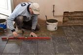 A Polish builder laying slate tiles in a domestic kitchen. - Timm Sonnenschein - 14-11-2011
