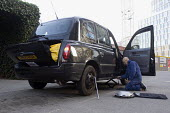 A taxi driver changing a flat tyre, replacing it with a spare. London. - Timm Sonnenschein - 2010s,2011,AUTO,AUTOMOBILE,AUTOMOBILES,AUTOMOTIVE,cab,cabs,car,cars,cas,cities,city,driver,drivers,DRIVING,employee,employees,Employment,flat,highway,job,jobs,LAB,LBR,maintaining,MAINTENANCE,male,man,