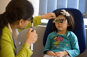 Consultant Optometrist checking a young girls eyes for astigmatism at the Birmingham NHS Paediatric Eye Service. - Timm Sonnenschein - 2010s,2012,asian,asians,BAME,BAMEs,Birmingham,BME,bmes,care,check,checking,checks,child,CHILDHOOD,children,cities,city,clinic,clinics,consultant,consultants,Consultation,CONSULTING,consulting room,def