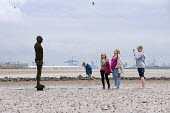 A mother with her children looking at Antony Gormley's Another Place Sculpture at Crosby Beach, Merseyside. - Timm Sonnenschein - 2010s,2011,ACE,adult,adults,Antony Gormley,art,arts,artwork,artworks,beach,BEACHES,boy,boys,cast,child,CHILDHOOD,children,coast,coastal,coasts,culture,daughter,DAUGHTERS,families,family,female,females