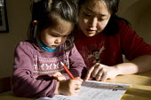 A girl practicing phonics for homework with the help of her mother, Birmingham. - Timm Sonnenschein - ,2010s,2012,adult,adults,asian,asians,BAME,BAMEs,BME,bmes,book,books,child,CHILDHOOD,children,chinese,cities,city,communicating,communication,daughter,DAUGHTERS,Diaspora,diversity,edu,educate,educatin