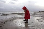 A girl playing in puddles and splashing about in the cold on beach, Baltic Sea, Germany - Timm Sonnenschein - 2010s,2011,BAME,BAMEs,beach,beaches,BME,bmes,child,CHILDHOOD,children,chinese,CLIMATE,coast,coastal,coasts,conditions,country,countryside,diversity,ethnic,ethnicity,eu,Europe,european,europeans,eurozo
