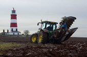 A Farmer ploughing a field and Happisburgh Lighthouse, Norfolk, East Anglia - Timm Sonnenschein - 2010s,2012,agricultural,agriculture,capitalism,capitalist,coast,coastal,coasts,driver,drivers,driving,EBF,Economic,Economy,employee,employees,Employment,farm,Farm Worker,farm workers,farmed,farmer,far