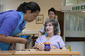 An NHS housekeeper and a rehabilitation assistant giving a drink to an elderly patient, Moseley Hall Hospital, Birmingham - Timm Sonnenschein - 25-07-2012