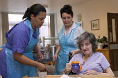An NHS housekeeper and a rehabilitation assistant giving a drink to an elderly patient, Moseley Hall Hospital, Birmingham - Timm Sonnenschein - 2010s,2012,age,ageing population,assistant,ASSISTANTS,Birmingham,care,cities,city,communicating,communication,conversation,conversations,dialogue,discourse,discuss,discusses,discussing,DISCUSSION,drin