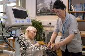 An NHS rehabilitation assistant measuring the blood pressure of an elderly patient, Moseley Hall Hospital, Birmingham - Timm Sonnenschein - 25-07-2012