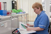 An NHS nurse checking the nutrition screening in a patient file, Moseley Hall Hospital, Birmingham - Timm Sonnenschein - 25-07-2012