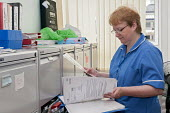 An NHS nurse checking the nutrition screening in a patients file, Moseley Hall Hospital, Birmingham - Timm Sonnenschein - 25-07-2012