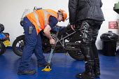 A P&O worker securing a Triumph Tiger 800 motorcycle to the deck aboard the Spirit of Britain cross-channel ferry before its departure from Dover to Calais - Timm Sonnenschein - 28-07-2012