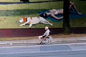 An old and disabled man in a wheelchair pushing himself down the road past a wallpainting of a , Essen, Germany - Timm Sonnenschein - 21-08-2012